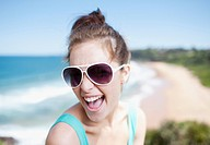 Woman in sunglasses laughing with ocean in background