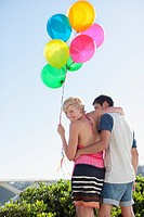 Couple with balloons hugging
