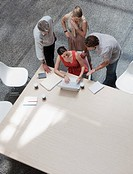 Directly above business people using laptop at conference table