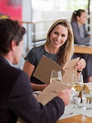 Man and woman looking at menus in restaurant