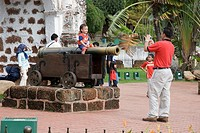 A father photographs his child sitting astride one of the Dutch cannons at the Portugese fort A´famosa Porta de Santiago Malacca