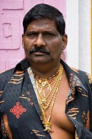 An Indian Malaysian making an ostentatious display of his wealth by wearing many gold chains