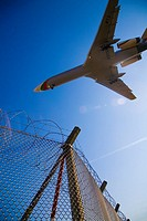 Aeroplane flying over security fence