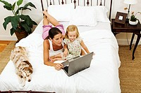 Mother age 29 and daughter age 4 in bed with pet dog Australian Shepard and working on a laptop computer