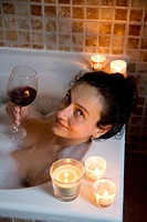 young woman having a bath with candles