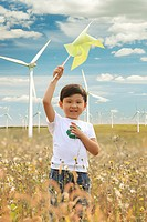 Boy holding pinwheel on wind farm,Boy holding pinwheel on wind farm,Contemporary