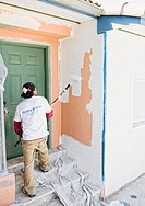 Latin man painting wall near front door