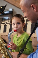 Father and daughter playing saxophone together