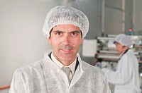 man wearing hair net and protective blouse at a food processing line looking to camera\n