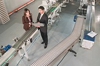 male and female managers standing near conveyor belts, looking at screen of laptop computer