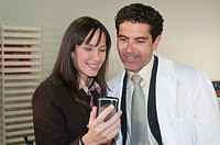 woman in business dress and man in white lab coat looking at screen of cell phone, smiling