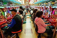 People playing Pachinko machines