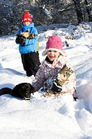 Children and dog collecting wood in snow