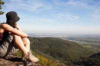 Woman sitting on mountain top