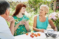 woman talks with mature couple in garden