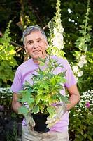 mature man holding plant.