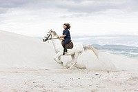 White horse, brown haired woman_rider, beach, sea, sand