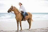 Brown horse, female_rider,beach, sea, sand