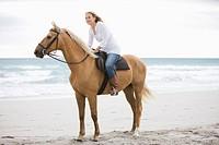 Brown horse, female_rider,beach, sea, sand