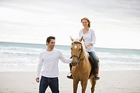 Brown horse, blond girl, dark haired teacher, man, beach, sea, sand
