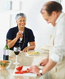 Woman with wine while man preparing food