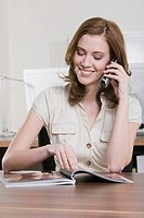 Germany, Munich, young woman in office using mobile phone, smiling, portrait