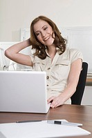 Germany, Munich, young woman in office, using laptop, smiling, portrait