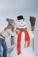 Germany, Bavaria, Munich, Young Woman Kissing Snowman, portrait