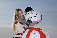 Germany, Bavaria, Munich, Woman making snowman, smiling, portrait