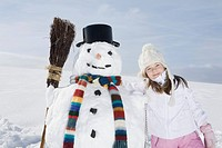 Germany, Bavaria, Munich, Girl 8_9 standing next to snowman, portrait
