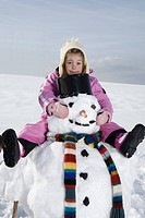 Germany, Bavaria, Munich, Girl 4_5 sitting on snowman, portrait