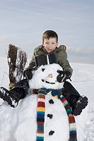 Germany, Bavaria, Munich, Boy 8_9 sitting on snowman, portrait