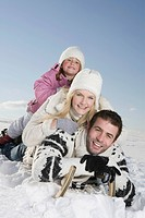 Germany, Bavaria, Munich, Family lying on sledge, smiling, portrait