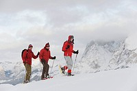 Italy, South Tyrol, Three people in a row, snowshoeing