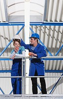Germany, Neukirch, Two Apprentice wearing hard hats, having a break