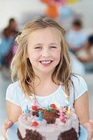 Girl holding birthday cake with a smile