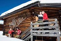 Italy, South Tyrol, Seiseralm, Log Cabin, Couple standing on balcony (thumbnail)
