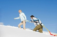 Italy, South Tyrol, Seiseralm, Couple walking in snow, pulling sledge