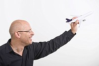 Businessman holding toy plane