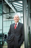 Germany, Munich, Businessman standing in office, hands in pockets, smiling