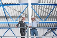 Germany, Neukirch, Man and woman architect standing in industrial hall, low angle view
