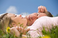 Germany, Bavaria, Munich, Young couple lying in meadow