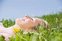 Germany, Bavaria, Munich, Young woman lying in meadow, eyes closed, portrait