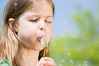 Germany, Bavaria, Munich, Girl 6_7 blowing dandelion seeds, eyes closed, portrait