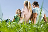 Germany, Bavaria, Munich, Family sitting in meadow, rear view