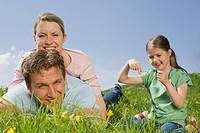Germany, Bavaria, Munich, Couple lying in meadow, Girl 6_7 holding flower