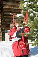 Italy, South Tyrol, Seiseralm, Boy 4_5 decorating Christmas tree in snow