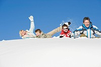 Italy, South Tyrol, Seiseralm, Family lying in snow, laughing, portrait