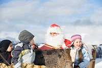 Italy, South Tyrol, Seiseralm, Santa Claus and children sitting in sleigh