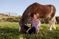 Girl sitting beside horse